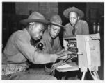 3 men working on a portable phone switchboard.